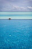 Lonely man relaxing in pool with sea in background in Dhigufinolhu Island, Maldives
