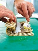 Sushi being made: wasabi being spread on a nori sheet