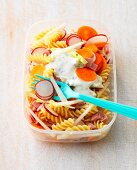 Pasta salad with vegetables and ham in a plastic box