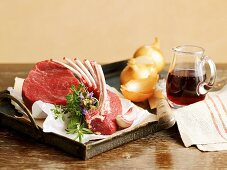 An arrangement featuring a saddle of lamb, beef, onions, herbs and red wine
