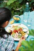 Frau isst Mexiko-Salat mit Mais und Hähnchenbrustfilets