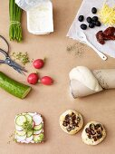 Bread with quark and cheese rolls topped with olives surrounded by ingredients