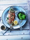 Stuffed trout wrapped in ham with sesame seed butter and mushy peas and parsnips