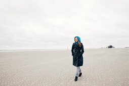 Woman wearing burberry coat standing relaxed on beach, wooden house in background
