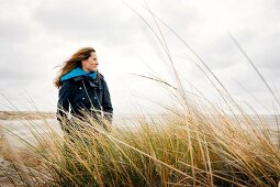 Woman wearing burberry coat standing relaxed between reeds on beach