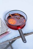 A saucepan of mulled wine and orange slices in the snow