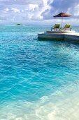 Two chairs on beach in island Veliganduhuraa, Maldives