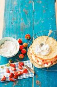 A layered sponge cake with cream and strawberries being made