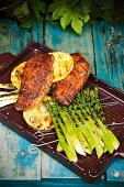 A tray of grilled duck breast fillets, green asparagus and pineapple slices
