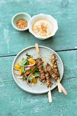 Oriental lamb skewers served with and onion and orange salad with mint and chickpea puree