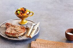 A pork chop with a pumpkin medley
