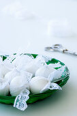 White eggs with lace ribbons in a bowl