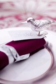 A Christmas place setting with a name card and a bird