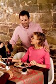 A couple eating Christmas dinner in a vaulted cellar