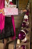 Frau mit Weihnachtsgeschenken auf einer Treppe