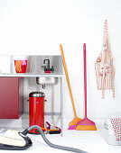 A sink, a bin, a Hoover, a broom, an apron and a bucket