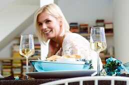A blonde woman sitting at a table laid for Christmas dinner