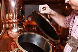 A brewer opening a copper kettle