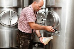 A brewer taking a sample of beer from a storage tank to measure the fermentation degree