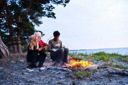 Frau und zwei Mädchen sitzen beim Lagerfeuer