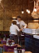 English restaurant in hall with exposed brick wall and hams hanging over historic counter