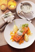 Salmon with a herbal foam sauce on carrot strips