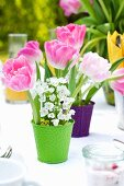 An arrangement of spring flowers featuring tulips on a laid table