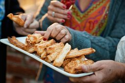 Hands taking cheese straws from tray