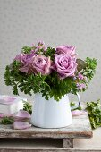 Bouquet of scented roses and pelargoniums in enamel jug