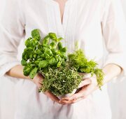 A woman holding three pots of herbs