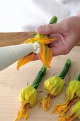 Courgette flowers being filled with ricotta