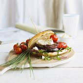 A grilled bread roll filled with vegetables and feta cheese