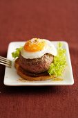 Toast topped with a burger and a fried egg