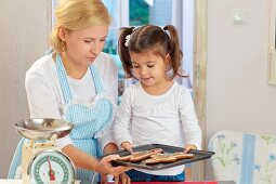 A mother and daughter baking gingerbread men