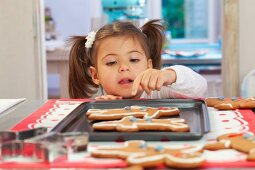 A little girl looking over a the edge of a table at gingerbread men on a baking tray