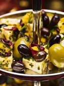 Manchego with black and green olives on a cake stand