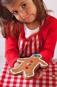 Little girl showing a gingerbread man