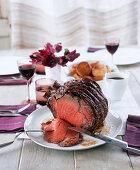 Roasted rib-eye steak on a laid table (England)