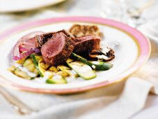Three Slices of Lamb Loins with Steamed Vegetables on a White Plate with a Pink Rim