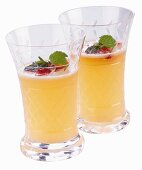 Two Glasses of Banana Slush Punch garnished with Raspberries and Mint