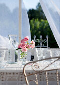 Roses in stemmed glass next to carafe of water and retro wine glasses on terrace table in front of translucent curtain