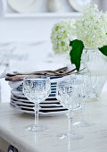 Crystal wine glasses in front of stacked plates and white flowers in glass vase