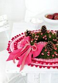 Autumnal moss wreath with pine cones and decorative mushrooms on a pink place mat