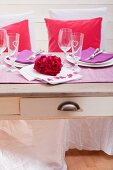 Festive table set with rose petals arranged in heart