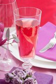 A glass of rosé sparkling wine on festive table