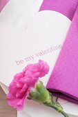 Place setting with carnation and heart-shaped Valentine's Day name card