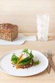 Vollkornbrot mit pochiertem Ei, Avocado und Babyspinat