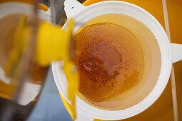 Honey being filtered through a fine sieve