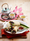 Pancake rolls with spicy duck, chilli sauce and tea (Asia)