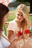 Two young women with drinks picnicking